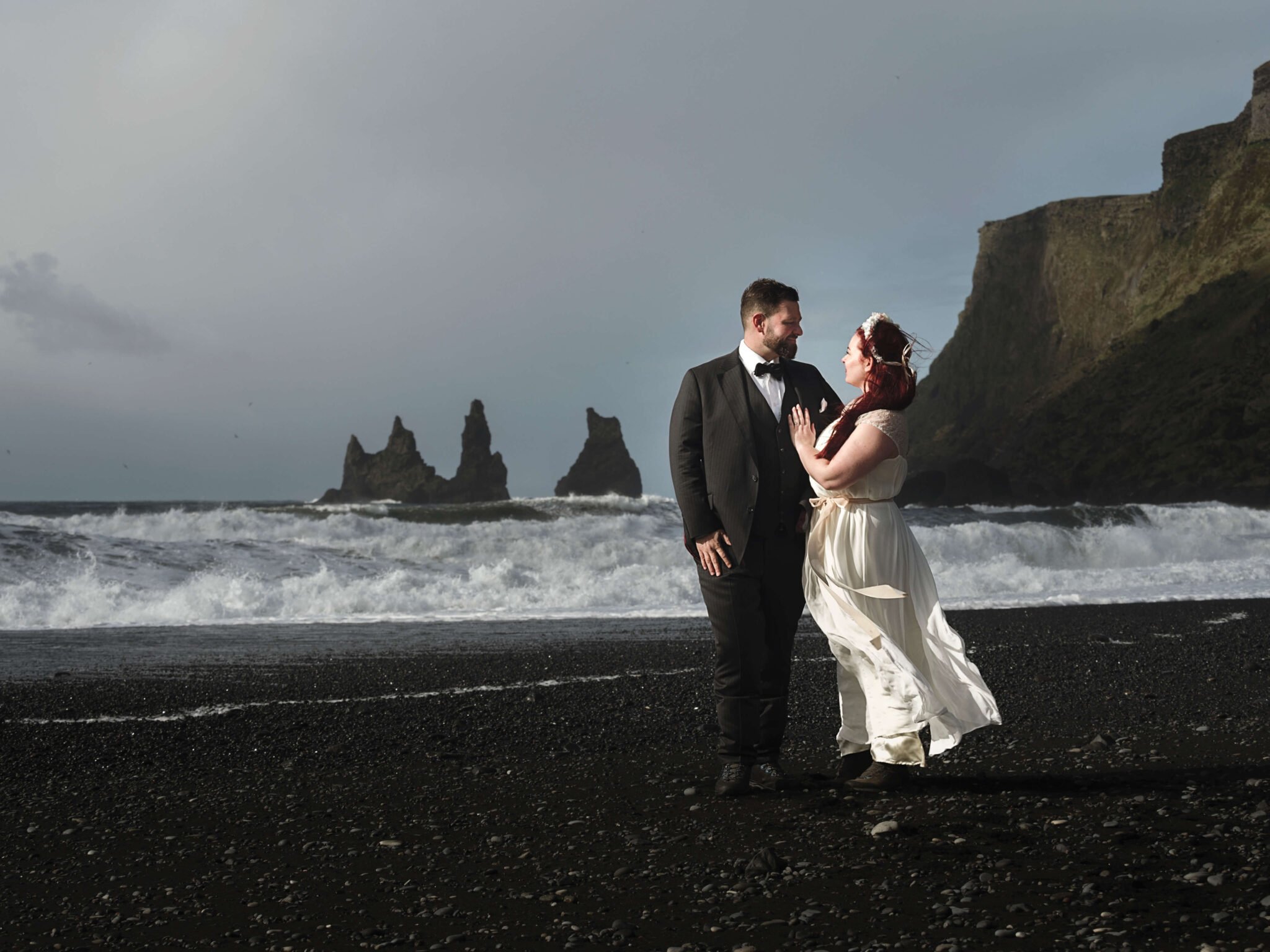 bride and groom looking at each other on the black sand beach in iceland