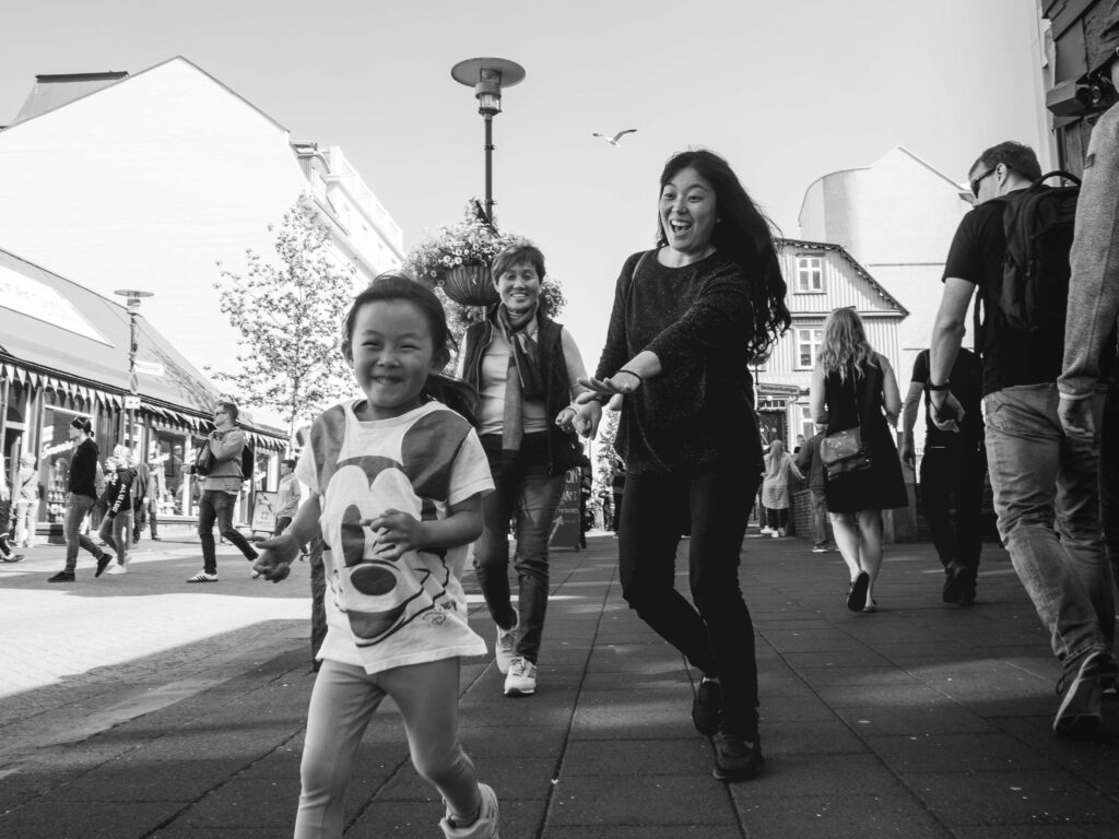 black and white photo of mother chasing her little daughter on the street