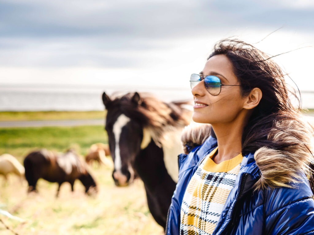 girl with sunglasses and with horses in the background