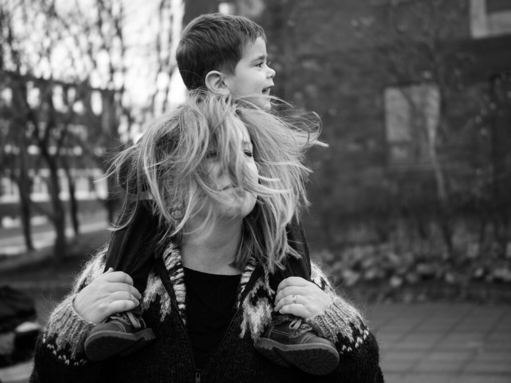 mom havng her son on her shoulders with messy hair black and white photo