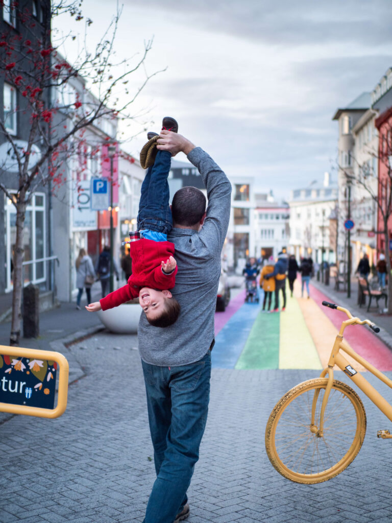 dad holding his son upside down on the family walk in reykjavik