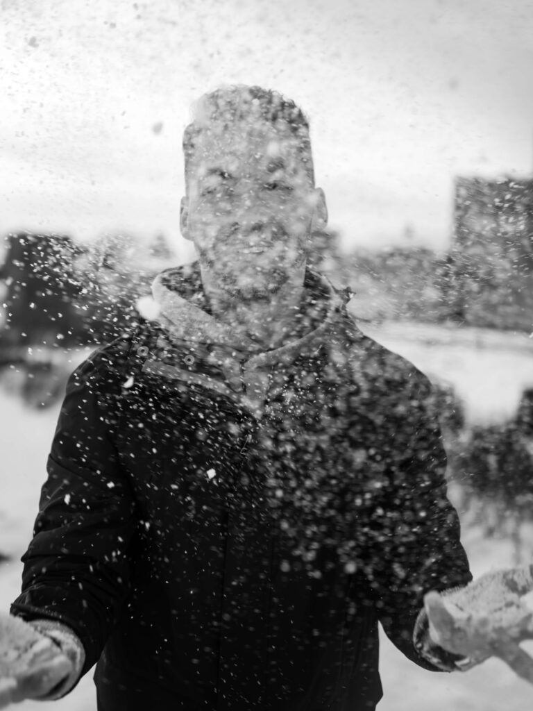 smiling man in the heavy snow blak and white photo