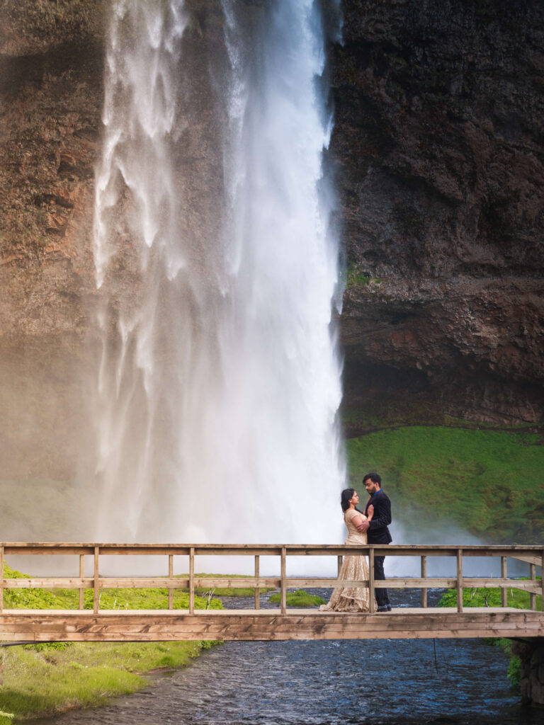 ndian couple in suit and golden dress looking at each other by waterfall in iceland