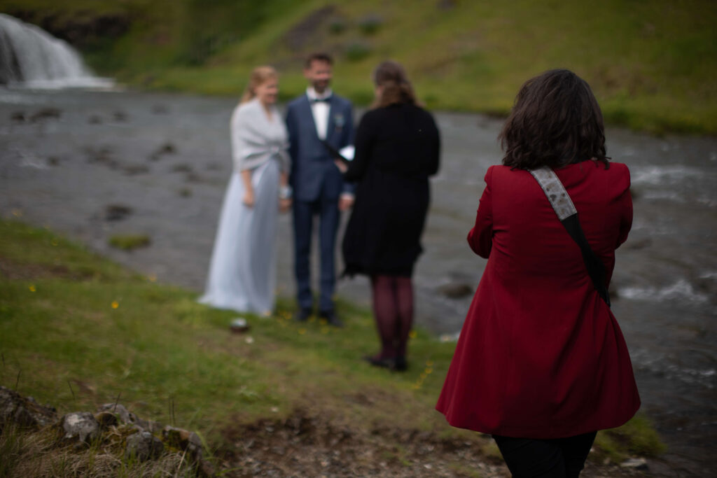 Kat deptula photography backstage photo during wedding cceremony elopement in iceland by the waterfall