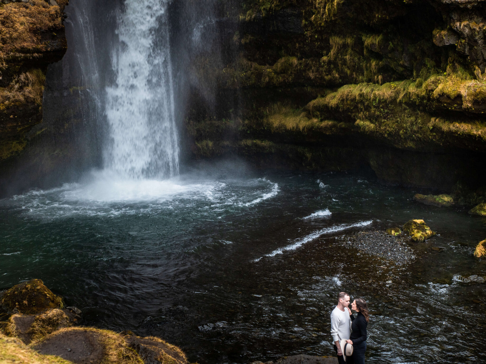 Engaged couple standing in front of Icelandic waterfall