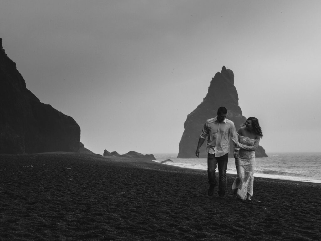 Black and white photo of the couple waling and laughing along black sand beach