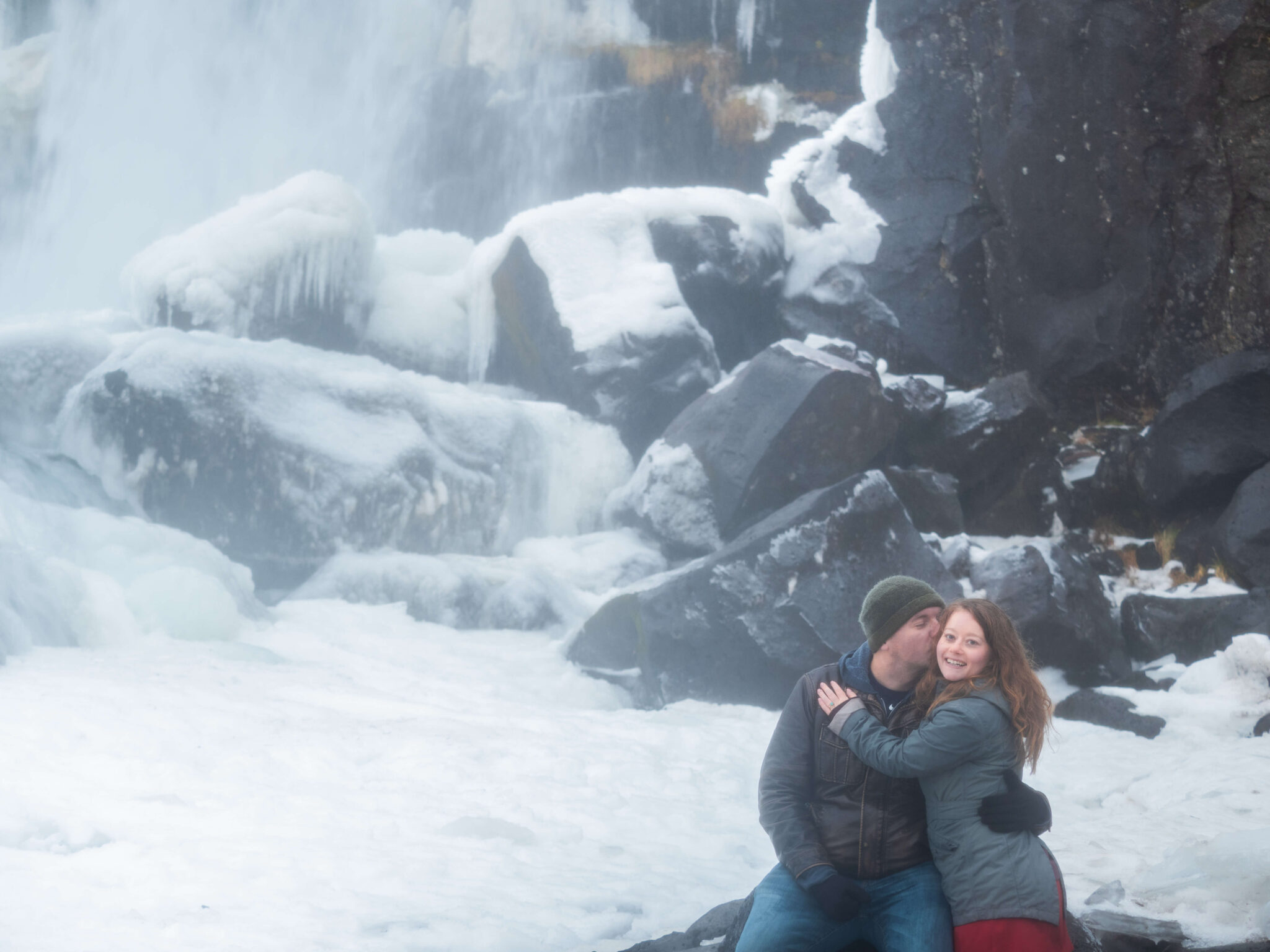 Couple hugging in front of waterfall
