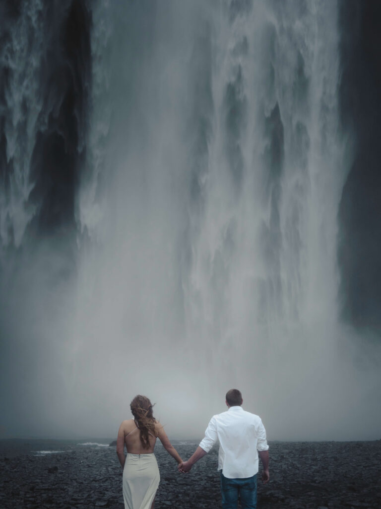 boy and girl standing in front of waterfall in cold weather