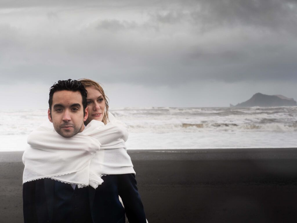 groom carryng bride on his back on black sand beach with white banket