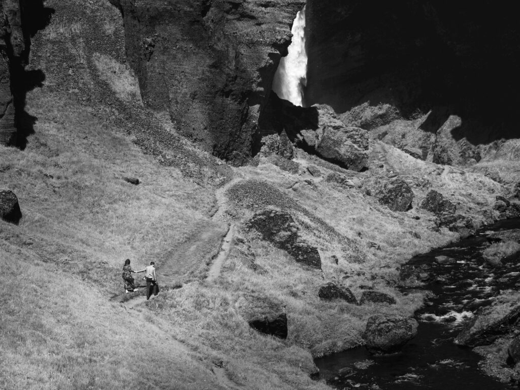 black and white photo of a couple hiking to the location of the photoshoot