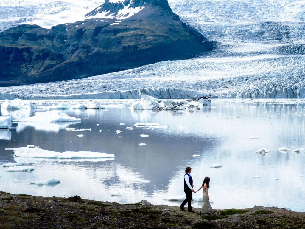 bride and grom walking along the glacier lagoon in Ieland with mountains in the background