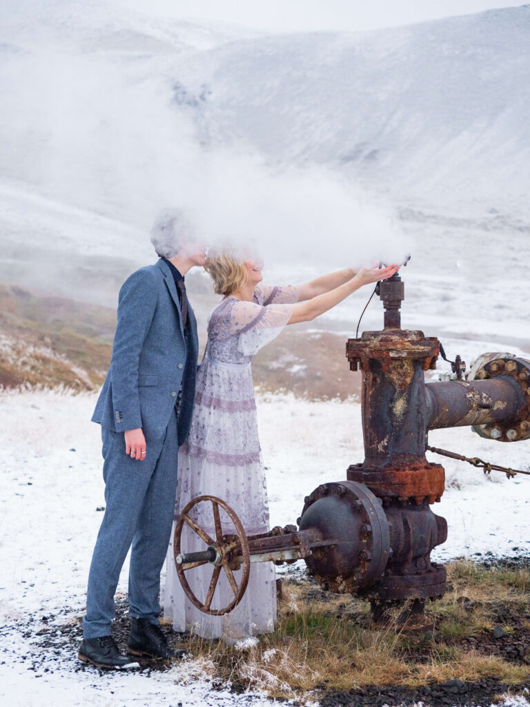 bride and groom playing with hot steam in hot river area in iceland