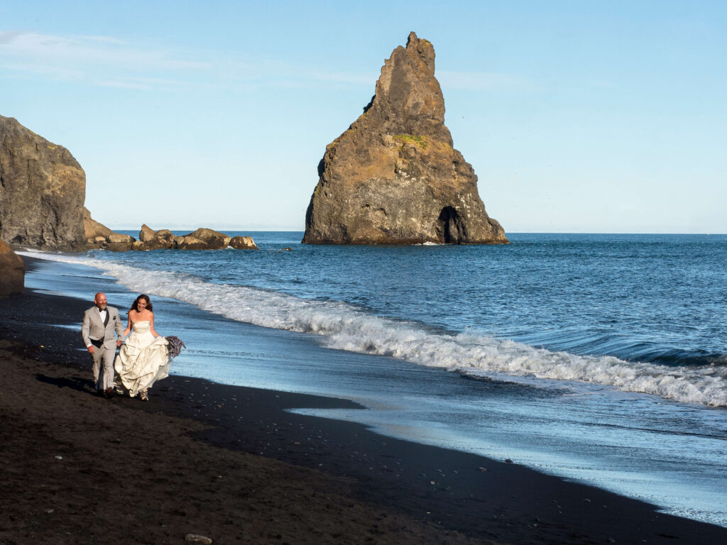 bride and groom in white dress and ligt suit on the black sand beach walking along the water