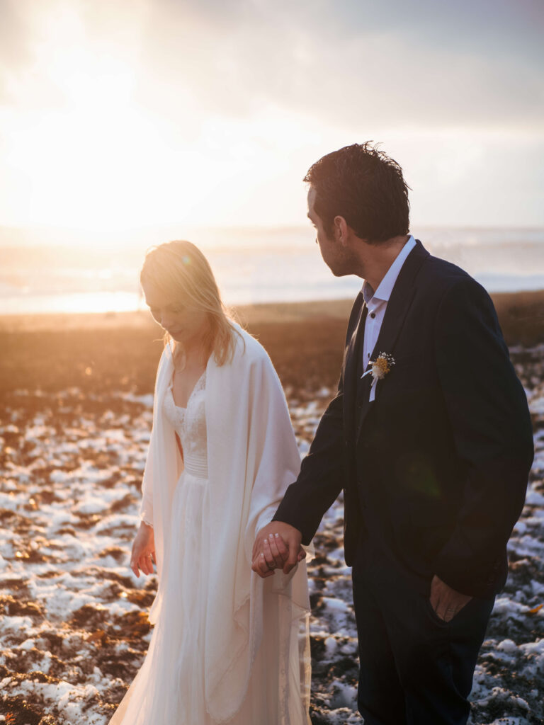 Golden hour photoshoot of bride and groom in black sand beach in iceland