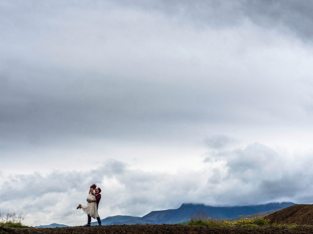couple in love posing in front of mountains in clouds in Iceland