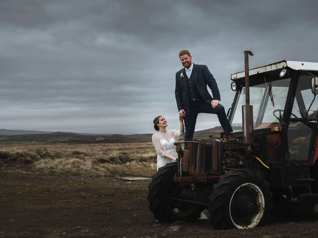 Groom standing on thetractor and wife looking ad him and laughing