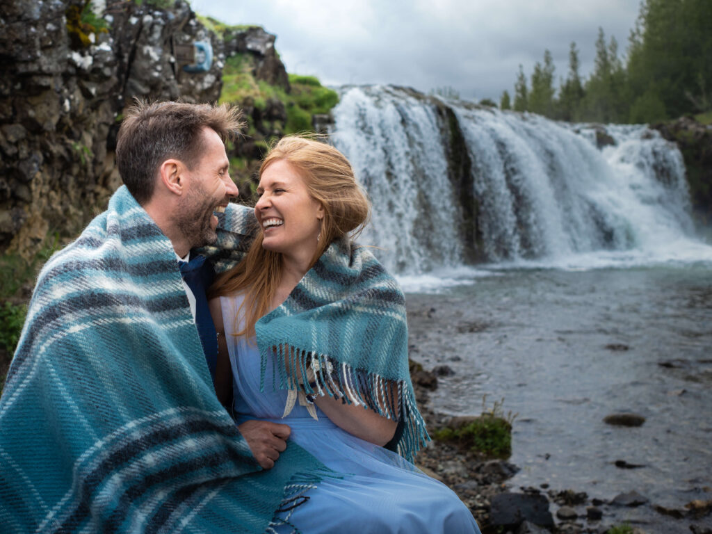 Just married in front of the waterfall with blanket