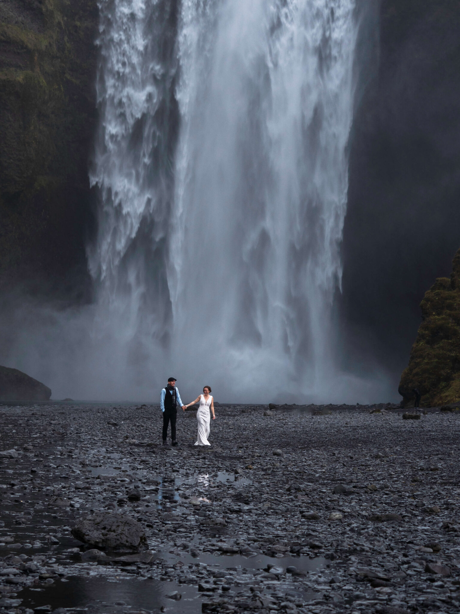 just married walking in front of the icelandic waterfall