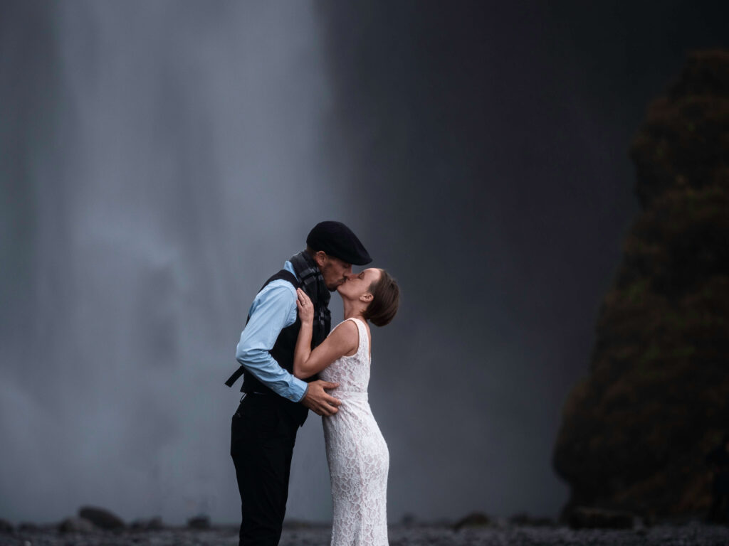 bride and groom kissing in front of waterfall in Iceland