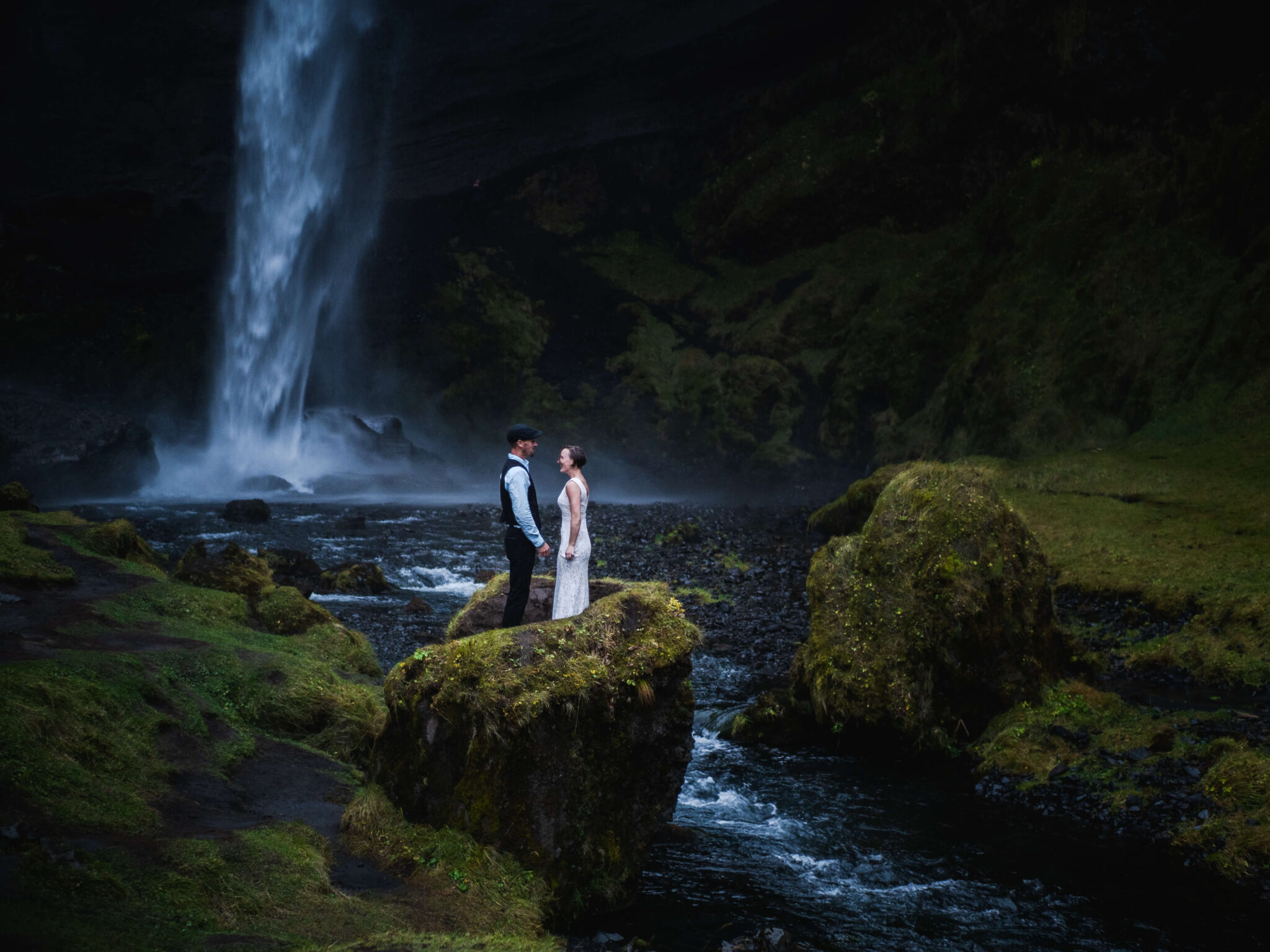 Newly weds standing in front of waterfall in Iceland