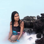 girl in the swim suit sitting in the water in blue lagoon iceland