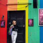 girl posing in from to rainbow wall