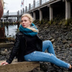 blond girl sitting in front of big boat in windy weather